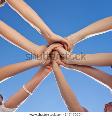 Teenagers showing unity and commitment all putting their hands to the centre of a circle against a sunny blue sky - stock photo