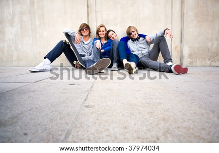 Teenagers Sitting by a Wall - stock photo