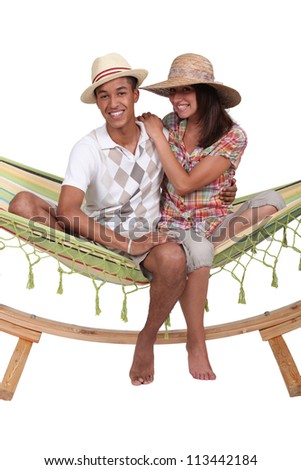 Teenagers sitting in a hammock - stock photo