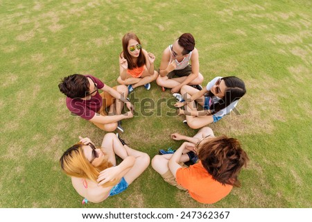 Teenagers sitting on the ground and talking with each other, view from above