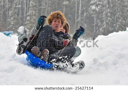 Teenagers sledding in the snow on a saucer. Winter fun. - stock photo