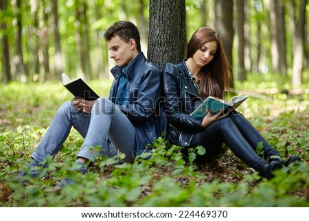 Teenagers students boy and girl reading outdoor in a forest
