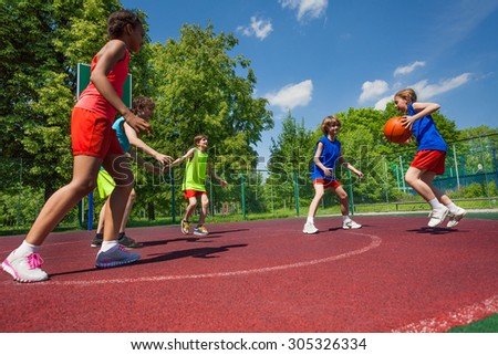 Teenagers team playing basketball game together - stock photo