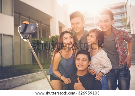 Teenagers using selfie stick to take photo