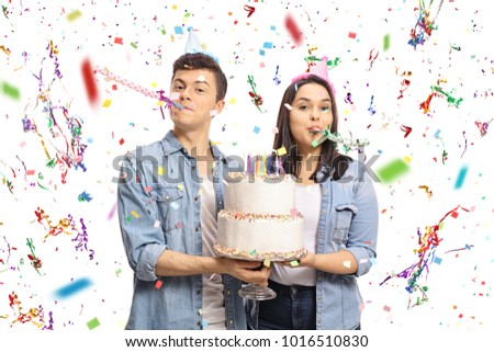 Teenagers with a birthday cake and party horns isolated on white background