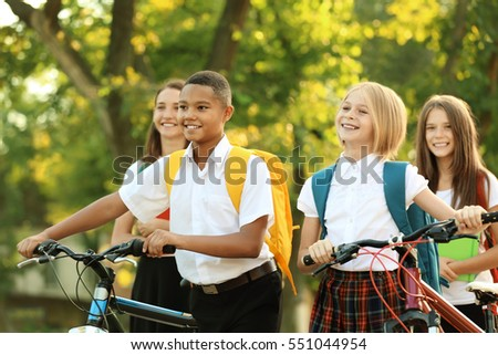 Teenagers with bicycles walking in park