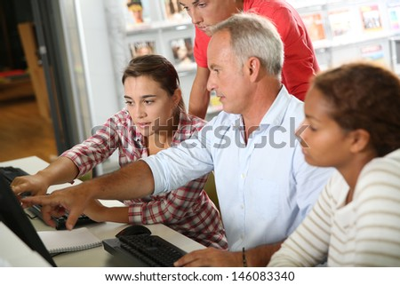 Teenagers with teacher in computers' class - stock photo