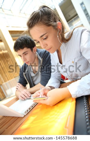 Teenagers working on laptop in school campus
