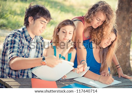 Teeneger students working together at park - stock photo