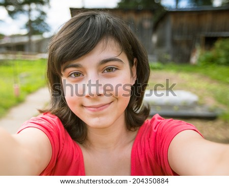 Teengirl taking a self-portrait out in the country house. - stock photo
