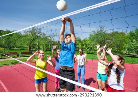 Teens all are with arms up play volleyball - stock photo