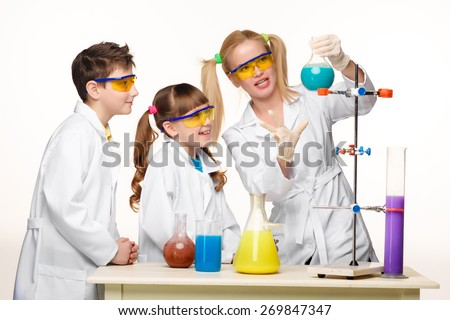Teens and teacher of chemistry at chemistry lesson making experiments isolated on white background