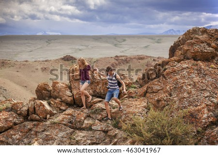 Teens boy and a girl come down from the mountain