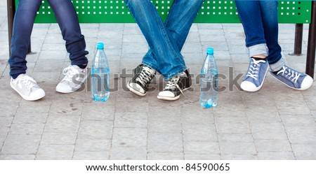teens in jeans and sneakers in street - stock photo
