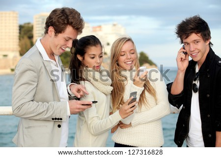teens talking or texting on mobile cell phones. - stock photo