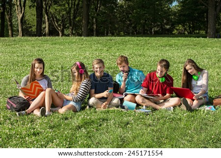 Teens with headphones and textbooks studying outdoors - stock photo