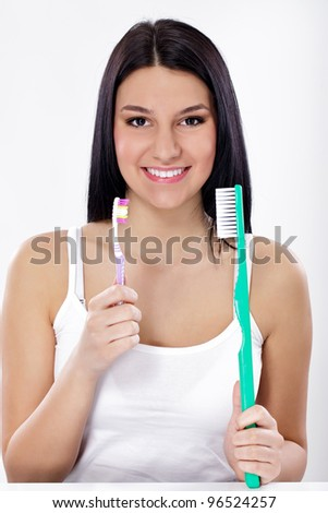 Teeth brushing, funny girl with small and big toothbrush