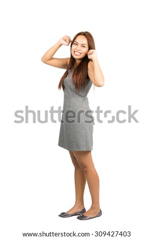 Teeth clenched Asian woman in gray dress with light brown hair, balled fists, looking at camera throwing immature temper tantrum, fed up, annoyed, irritated. Thai national of Chinese origin.