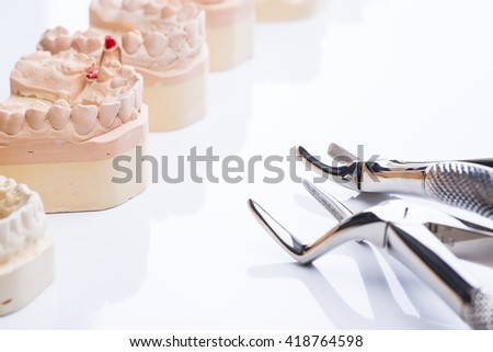 Teeth molds with basic dental tools on a bright white surface - stock photo