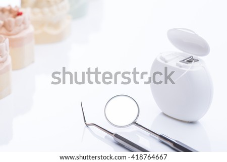 Teeth molds with basic dental tools on a bright white surface