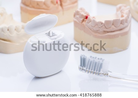 Teeth molds with dental floss and brush on a bright white surface - stock photo