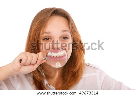 Teeth of young woman through magnifier, isolated on white background. - stock photo