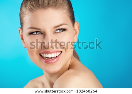 Teeth whitening and treatment. Portrait of beautiful Caucasian female model with perfect and healthy smile over blue background.  - stock photo