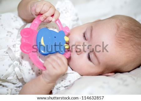 Teething baby playing with teether toy