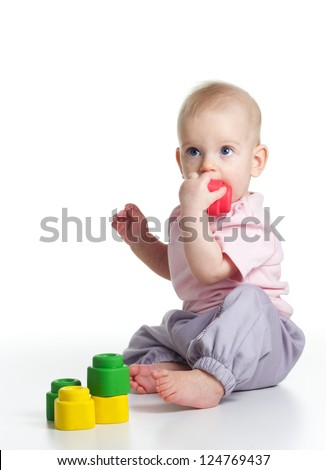 Teething blond baby bites colored toy on white background