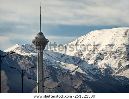 TEHRAN - APRIL 1: Milad Tower of Tehran in front of snow covered Alborz mountains on April 1, 2014 in Tehran, Iran. Milad Tower is the second most famous landmark of Tehran after Azadi Monument. - stock photo