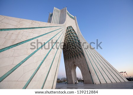 TEHRAN - FEBRUARY 11: Side view of Azadi Monument in daylight against blue sky on February 11, 2012 in Tehran. Azadi Monument is the most famous landmark of Tehran situated in the center of Azadi sq. - stock photo