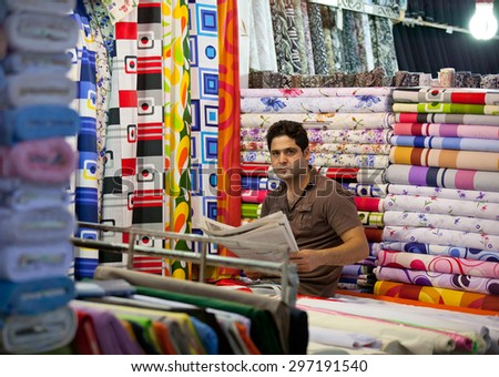 TEHRAN, IRAN - AUGUST 04, 2011: Unknown young man trades fabrics in traditional Grand Bazaar of Tehran, which is a historical market and one of the important tourist attractions of Tehran. - stock photo