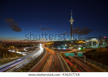 TEHRAN, IRAN - DECEMBER 4, 2015: Illuminated Milad Tower behind highways of Tehran filled with passing cars. Milad Tower is the second most important landmark of Tehran, after Azadi Monument. - stock photo