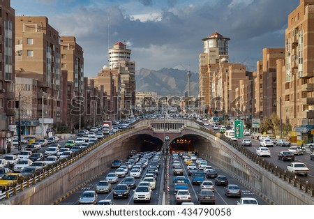 TEHRAN, IRAN - FEBRUARY 19, 2016: Heavy Traffic Congestion in and around Tohid Tunnel with Milad Tower and Alborz Mountains in Background. Tohid is the third longest urban tunnel in Middle East. - stock photo