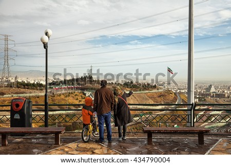 TEHRAN, IRAN - FEBRUARY 11, 2015: Iranian family with their son staring at skyline of Tehran from a high ground Park. Tehran is capital of Iran and its most populated city. - stock photo