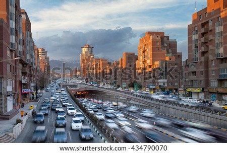 TEHRAN, IRAN - FEBRUARY 19, 2016: Tehran Cityscape with Cars Passing Through Tohid Tunnel in Front of Sunlit Navvab Buildings. Tohid Tunnel is the third longest urban tunnel in Middle East. - stock photo