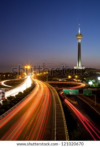 TEHRAN, IRAN - JULY 16: Illuminated Milad Tower and light trails of cars on July 16, 2011 in Tehran, Iran. This is a night shot from streets of Tehran, with its famous Landmark, the Milad Tower. - stock photo