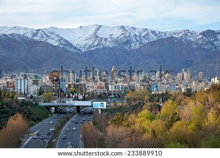 Tehran skyline and greenery in front of snow covered Alborz Mountains as viewed from atop of Nature Bridge. - stock photo