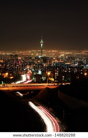 Tehran skyline illuminated at night with motion blur of cars - stock photo