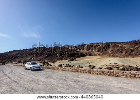 TEIDE, TENERIFE, SPAIN - DECEMBER 2015: Car parking among volcanic hills at Teide National par on Tenerife island, Spain - stock photo