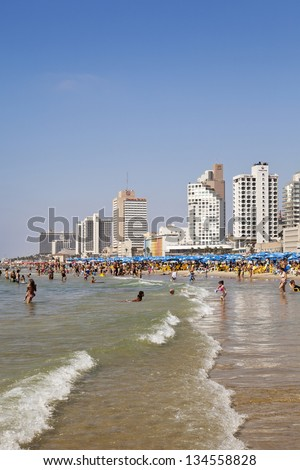 TEL AVIV - AUGUST 18: View of hotels and the beach, packed with people sunbathing or cooling in the sea's water. On August 18 2012 in Tel Aviv, Israel.