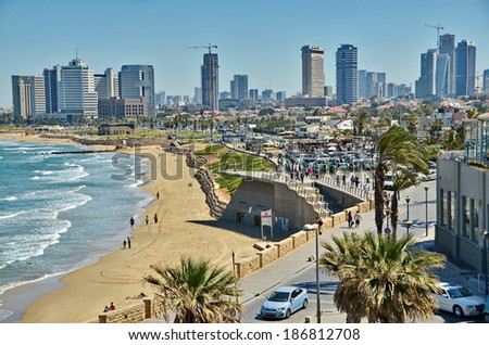 TEL AVIV, ISRAEL - APR 11, 2014:People on the Mediterranean  beach and Tel Aviv, Israel boardwalk with the city sky line and towers in the background on a late spring / early summer day