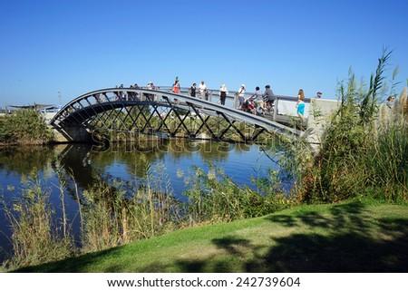 TEL AVIV, ISRAEL - CIRCA OCTOBER 2014 People on the bridge on the Yarkon river                                - stock photo