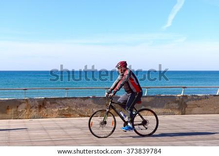 TEL AVIV, ISRAEL - FEBRUAR 4, 2016:Israeli elderly man rides a bicycle along Tel-Aviv beach.  - stock photo