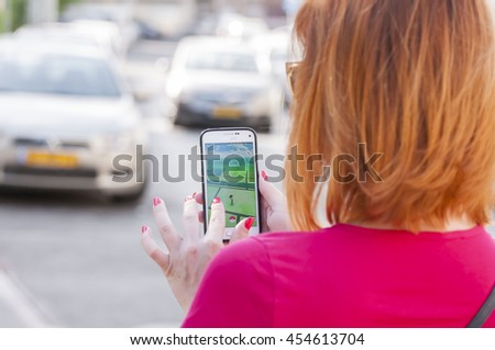TEL AVIV, ISRAEL. July 19, 2016. Red headed girl risking her life playing the popular Pokemon GO game on her mobile phone in the street. - stock photo