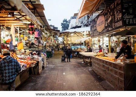 TEL AVIV, ISRAEL - MARCH 23, 2014: Shoppers at the Carmel Market in Tel Aviv on March 24, 2014, Israel. It's one of Israel's oldest outdoor marketplaces offers a wide variety of foods and merchandise. - stock photo