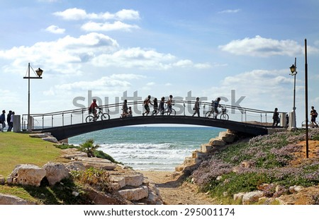 TEL AVIV, ISRAEL - MAY 19, 2014: Pedestrian bridge with pedestrians and cyclists on the promenade in Tel Aviv - stock photo