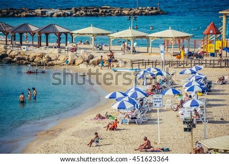 Tel Aviv, Israel - October 18, 2015. People sunbathes on the beach next to Hilton Hotel in Tel Aviv - stock photo