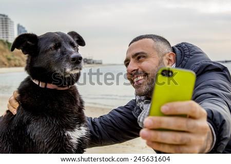 Tel-Aviv - January 19,2014: Man helping his grumpy dog friend to take a social media selfie image using a smartphone - stock photo