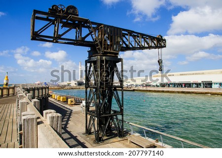 TEL-AVIV - JULY 25, 2014: A restored old crane, with restaurants and commercial area in the background, in Tel-Aviv Port, Israel. The port compound was restored as a dining and commercial area